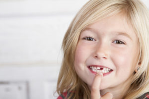Girl smiling with missing tooth, baby teeth